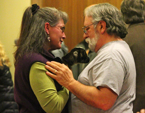 Lacia Bailey, with her pet goat, speaks with Paul Schulte, brother of Dennis Schulte, during a Thursday prayer vigil at Sand Point Community United Methodist Church in Seattle for Karina Ulriksen-Schulte and her son, Elias Schulte. (Ken Lambert/The Seattle Times)