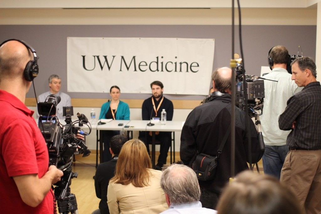 Members of the media clustered around Dr. Francois Aspesberro, Marilyn Schulte, and Dan Schulte (left to right) at today's press conference at Seattle Children's.